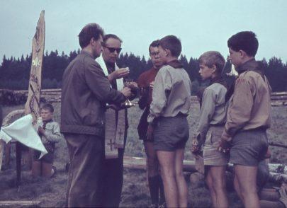 Otec Stanislav Krátký podává svaté přijímání při mši svaté na skautském táboře v Klášterci nad Orlicí v srpnu 1969 (foto J. Němec – Fakír, Archiv 91. oddílu Junáka, Brno).